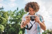 Spodní pohled záběr kavkazské člověka s kudrnatými vlasy, kontrola fotografie v jeho digitální fotoaparát. Mladý pohledný muž nosí ležérní košile s digitální fotografie fotoaparát stojí na pozadí přírody. Lidé, cestování
