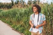 Fotografie Reisen, Menschen und Lebensstil-Konzept. Kaukasisch lächelnden jungen schönen Reisenden männlich trägt in lässig mit lockigem Haar, mit Digitalkamera, um ein paar Fotos von der Natur zu machen, Blick in die Kamera.