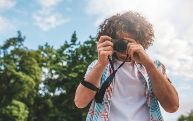 Young tourist male with digital camera taking photos, on a nature and sky background. Handsome man curly hair exploring nature on vacation trip. Travel, people and lifestyle concept stock vector