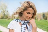 Érzéki nő, a szőke haj fúj, és mosolyogva néz portréja. Vértes portréja kaukázusi fiatal nő mosoly kézzel szeles szőr a parkban. Emberek, életmód fogalma