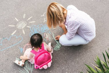 Top view of cute little girl and her mother drawing with colorful chalks on the sidewalk. Caucasian blonde female play together with her kid preschooler with backpack outdoor. Mom and child activity