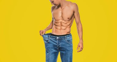 Horizontal studio image of young Caucasian fit man wearing big blue jeans after diet, showing sexy torso. Attractive man posing on yellow background after losing weight. Copy space. Healthy lifestyle