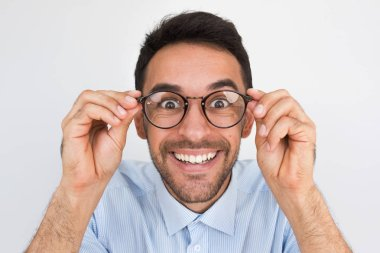Closeup shot of amazed young European handsome male, looking through round spectacles, touches rim of glasses, smiling with healthy toothy smile posing in studio. People, emotion and lifestyle concept