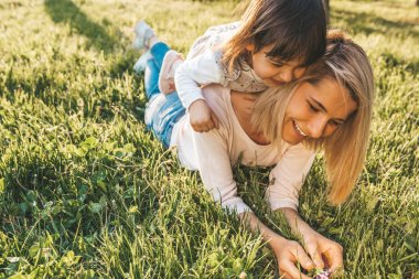 Attractive happy young mother lying with her cute daughter on grass in the park. Happy family relationship. Cheerful woman playing with her child outdoor, explore nature. Motherhood and childhood.