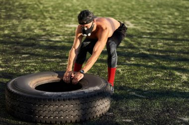 Muscular young male with mask doing exercises with big tire outdoors in stadium. Shirtless sportsman doing hard workout, healthy lifestyle. People and sport concept.