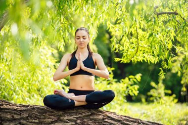 Attractive beautiful woman practitioners yoga on nature, park, forest. Lotus position. Yoga, Sport. Meditation.