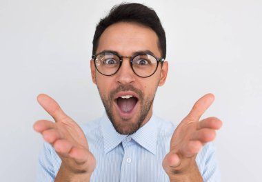 Closeup portrait of surprised unshaven young male gesture with hands and opens mouth with joyful expression, expresses positive emotion, isolated over white studio background. People concept