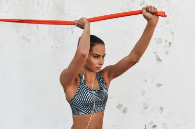 Horizontal image of pretty woman runner standing against concrete wall doing stretching exercises holding a red resistance band. Athletic woman in fitness clothes doing exercises outdoor.