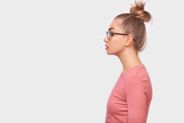 Side view portrait of young pretty woman in eyewear, looking away to the blank copy space, isolated over white wall. Caucasian female with hair bun wearing pink blouse having serious expression