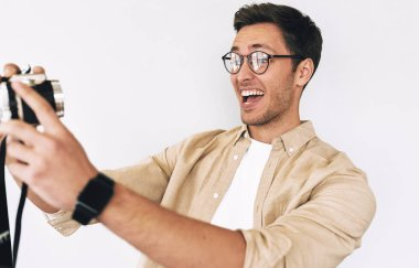 Cheerful happy man taking selfie over white studio background. Young male smiling and wearing eyewear making self portrait using digital camera.