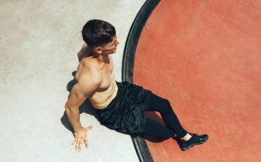 Above view image of athlete muscular young man resting after workout, sitting on sportsground. Healthy and fit male taking a break after exercising outdoors. People and sport concept