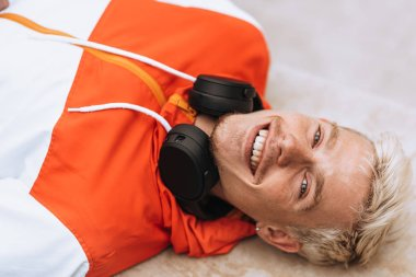 Above view image of handsome young smiling man with happy expression with toothy smile, looking at the camera with headphones on the neck lying on stairs outdoors. Lifestyle, people, music concept