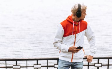 Handsome young blond man enjoying weather in city park waiting for his girlfriend, texting message while listening to his favorite music from wireless headphone using smart phone outdoor in the park.