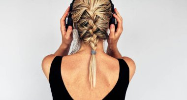Rear view image of a blonde young woman touching her headphones during listening to music. Horizontal back view of pretty female in black dress with braid hairstyle listens to audiobook in headphones.