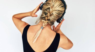 Studio rear view shot of attractive blonde young woman dancing and touching her headphones during listening to music. Beautiful female in black dress with braid hair listens to audiobook in headphones