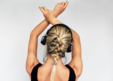 Studio rear view image of relaxing beautiful blonde young woman dancing during listening to music in headphones. Pretty female in black dress with braid hair listens to favorite songs in headphones