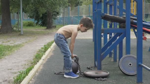 Little boy lifting heavy kettlebell on the outdoor sports ground