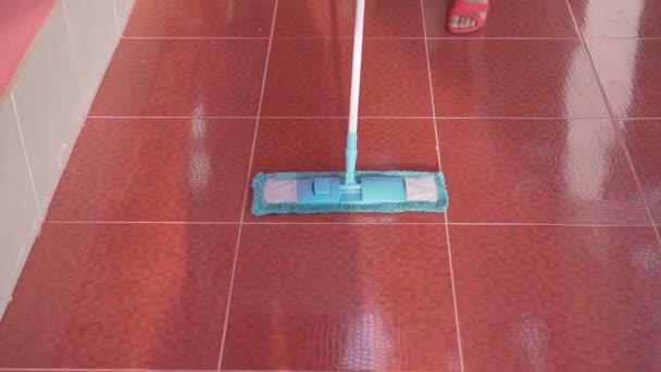 Žena čištění červenou podlahu s mopem modré mikrovlákno