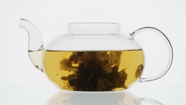 exotic green tea with flowers in glass teapot on white background