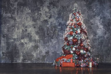 Decorated christmas tree over concrete wall