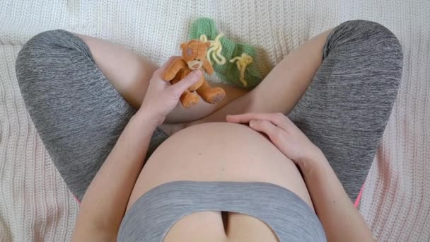 Pregnant Woman holding small teddy bear for her baby, Maternity or motherhood concept