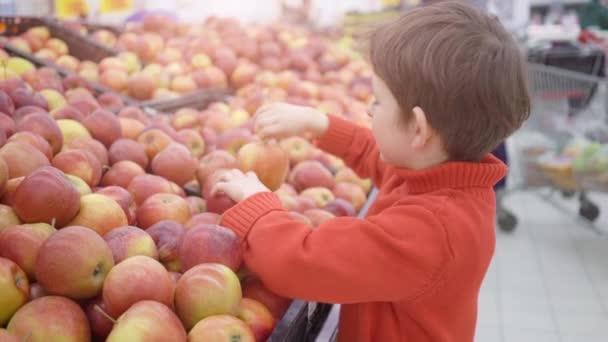 Vicces kisfiú szedés almát a dobozból, a családi vásárlás során a hipermarket
