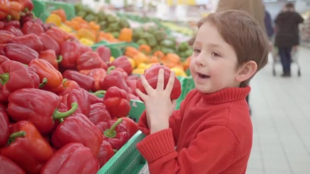 little boy in supermarket smelling red bulgarian peppers. Shopping in store, fresh products for kitchen and cooking.