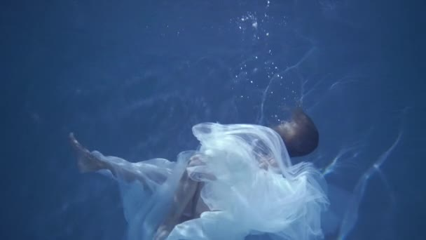 Woman with long hair in a white dress floating in blue water