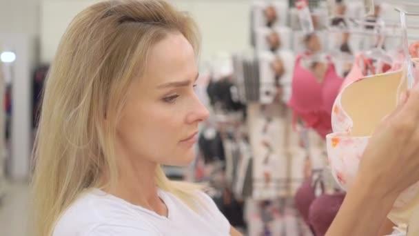 Žena výběru nové podprsenky v obchodě se spodním prádlem