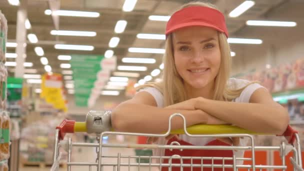 Smiling saleswoman in red uniform leaning on a shopping cart and looking at the camera