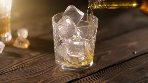 Barman pouring whiskey in a glass with ice on a wooden table