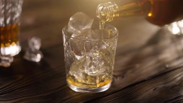 Az üveg és a jégkocka poharából töltött whisky, rusztikus, fából készült asztalokkal tálalva