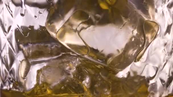 Pouring scotch whisky in glass with ice cubes in slow motion