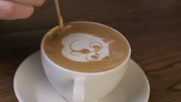 ruka baristy, která dělá Latte umění