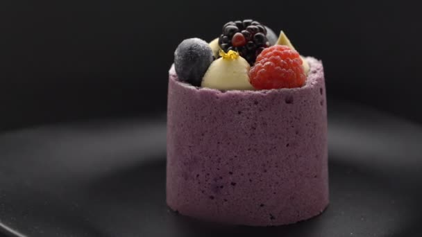 Delicious cake with blueberry mousse and fresh raspberrie and blueberryrotating on black plate