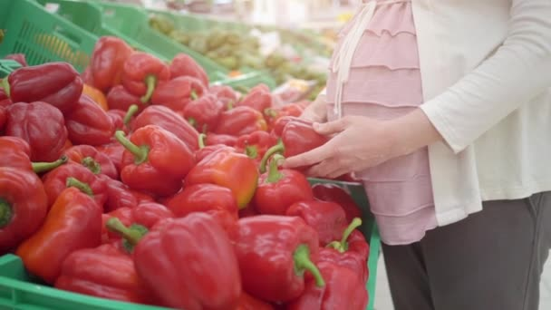 Young pregnant woman choosing red pepper in a vegetable store