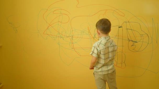 Kleiner Junge malt zu Hause an die Wand