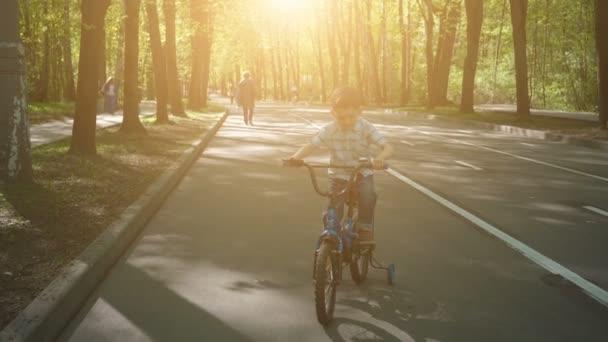 Šťastný chlapec na kole na asfaltové silnici. Milý chlapec, který se učí jezdit na kole na cyklistické dráze.