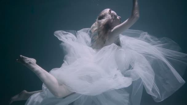 Beautiful woman swimming underwater in white elegant dress