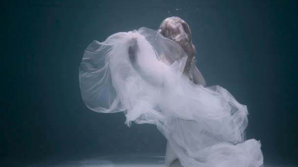 schöne Frau schwimmt unter Wasser im weißen eleganten Kleid