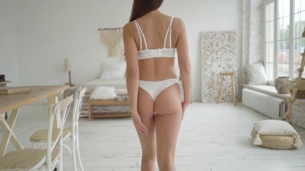 Seguimi. Giovane donna sexy in lingerie bianca in camera da letto leggera.