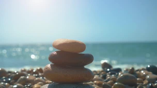 Hand building stones pyramid on pebble beach, stability, zen, harmony, balance concept