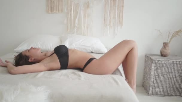Young and beautiful woman in sexy black underwear posing in the bed