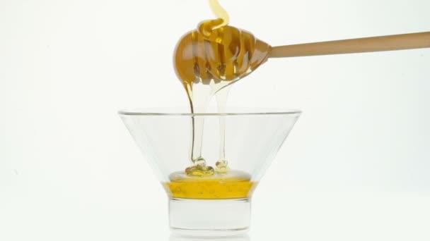 Skleněná mísa s nalévání medu a dřevěné tyčinky na bílém pozadí