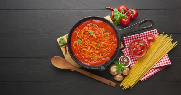 Cooking noodles with tomato sauce in cast iron pan served with red chili pepper, fresh basil, cherry-tomatoes and spices over black rustic wooden background.