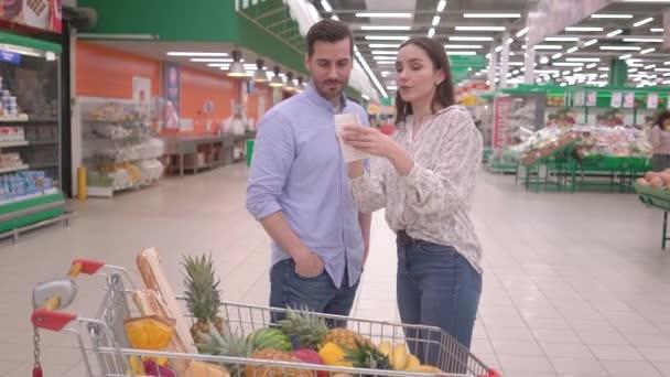 Atraktivní šťastný tisíciletý pár nakupování v supermarketu s nákupním vozíkem, kontrola účtenky za nákup potravin, krásný manžel a manželka kupující spokojenost zákazníka obchod koncept