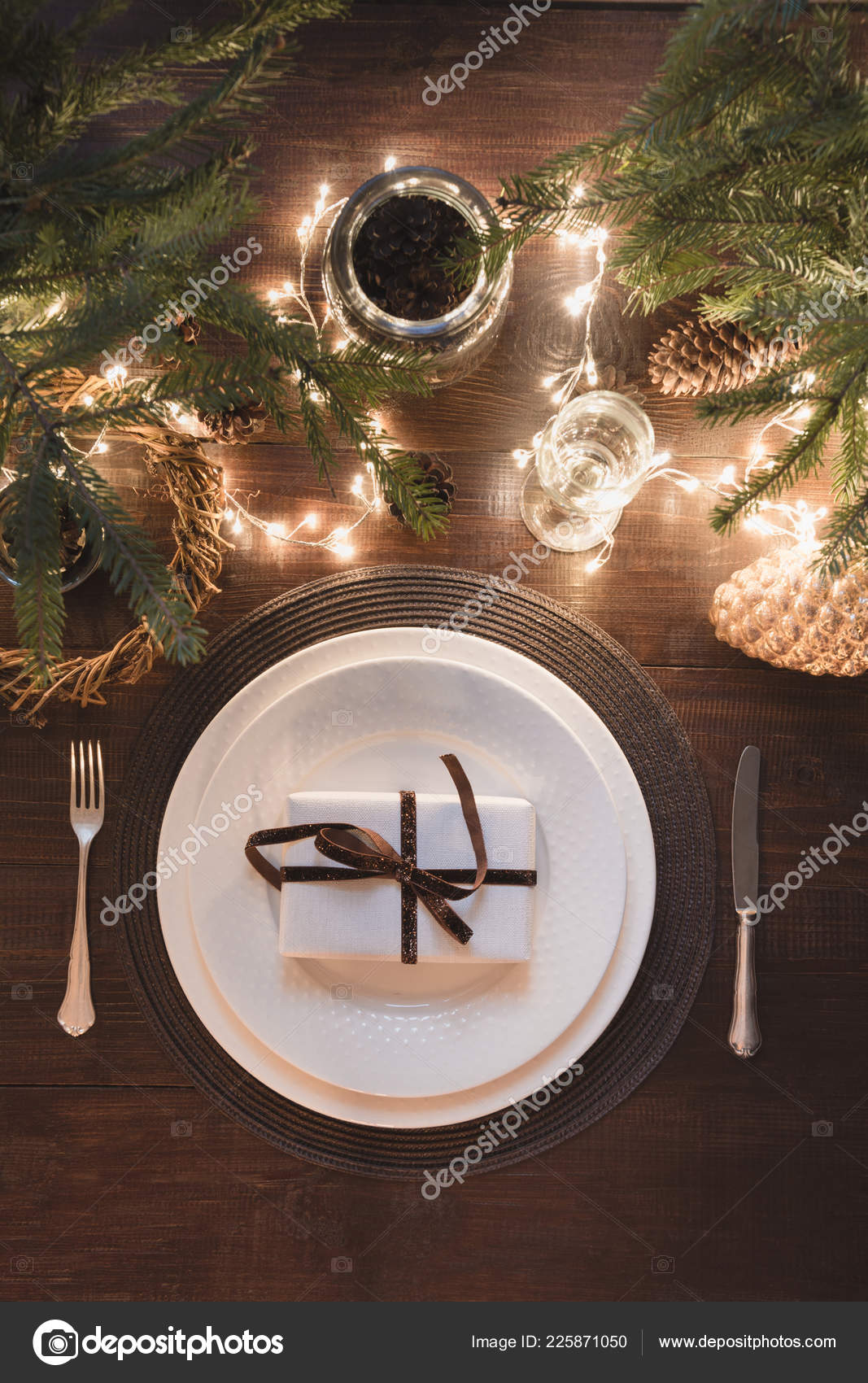 Christmas Table Setting With Silverware Garland And Evergreen Decor