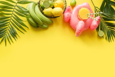 Tropical frame of fruits, banana, lime, leaves palms, orange juice in inflatable pink flamingo on punchy pastel yellow background.
