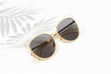 Stylish sunglasses with bright sunlight and shadow from palm leaves. Summer vacation concept.