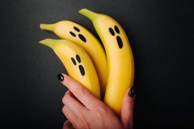 female hand holding Banana Ghosts Halloween Treats